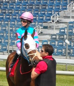 Assistant starter Chris Campitelli leads a horse into the gate.  Photo by Teresa Genaro.