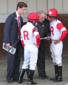 Ken Ramsey, center, and his grandson Nolan go over race strategy with riders Joel Rosario and Shaun Bridgmohan before the Virginia Derby.  Photo by Nick Hahn.