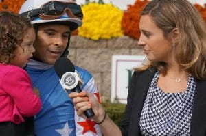 Richard Monterrey holds daughter Daniella while talking with Gabby Gaudet after winning the Maryland Million Nursery aboard It's a Bang.