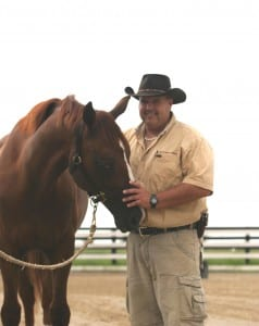 Kerry Thomas visits with a horse.  Photo courtesy of Thomas Herding Technique.