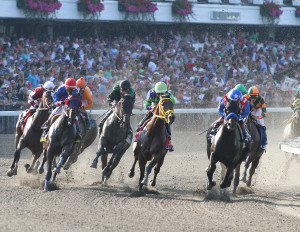 The field enters the first turn in the Haskell with Bayern along the inside. Photo By Ryan Denver/EQUI-PHOTO.