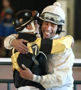 Kendrick Carmouche (right) and John Bisono embrace after dead-heating for the win in the Auld Lang Syne S. Photo By Bill Denver/EQUI-PHOTO
