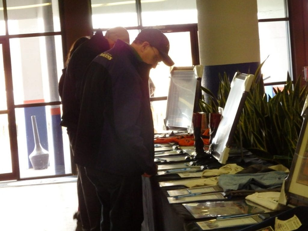 Racing fans look over some of the auction items during the Fundraiser for Fray. Photo by The Racing Biz.